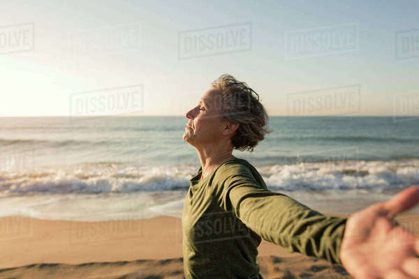 Side view of woman with arms outstretched at beach against clear sky Royalty-free stock photo