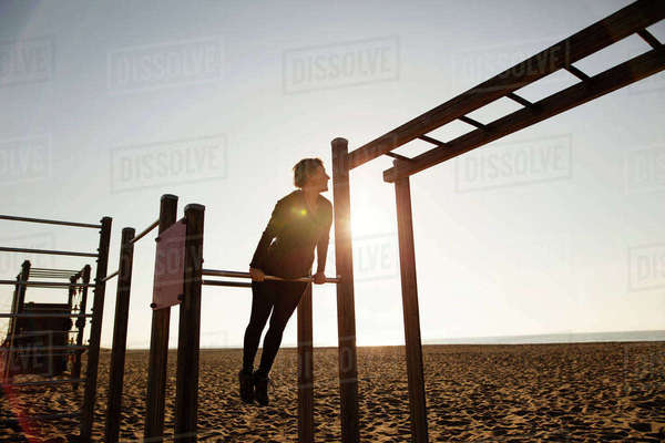 Woman exercising on gymnastics bars at beach against clear sky Royalty-free stock photo