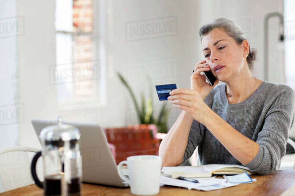 Woman holding debit card while using phone at home Royalty-free stock photo