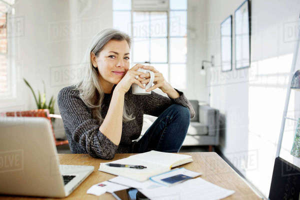 Portrait of woman holding coffee mug while working at table in living room Royalty-free stock photo