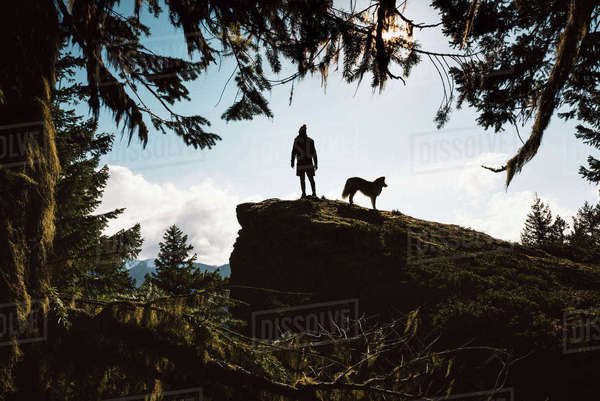 Low angle view of silhouette man with dog standing on mountain against sky Royalty-free stock photo