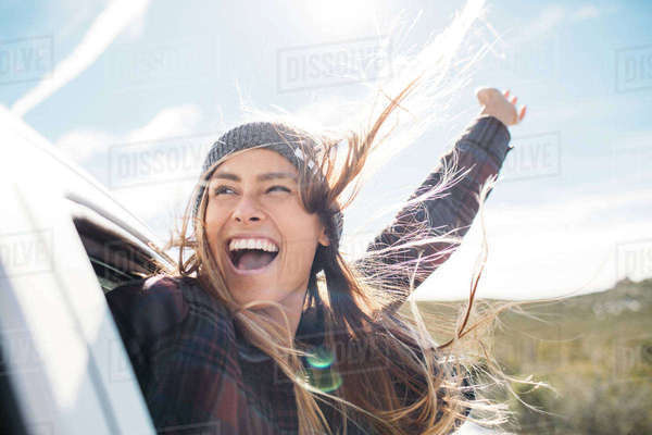 Cheerful young woman enjoying in car against sky Royalty-free stock photo