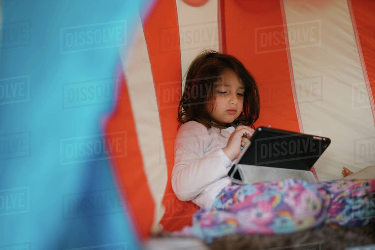 Four-year-old girl in pajamas looking at tablet in a little house Royalty-free stock photo