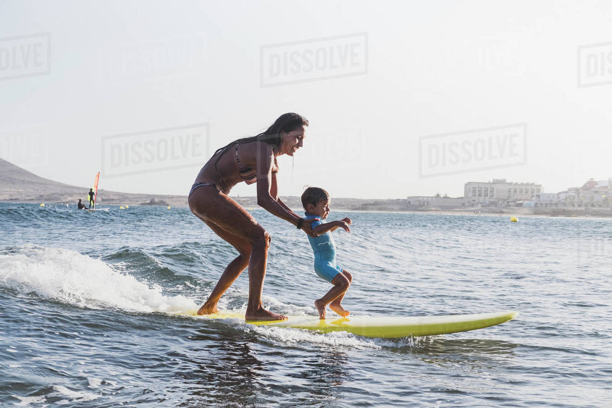 Full view of mother and son surfing a small wave at sea Royalty-free stock photo