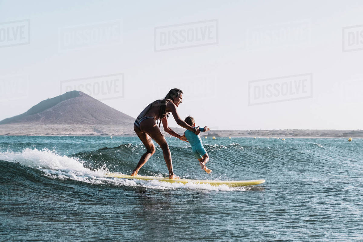 Full view of surfer mother surfing a small wave with her son Royalty-free stock photo