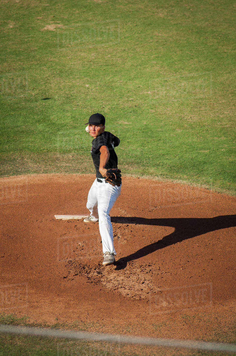 Teen baseball pitcher in black and white uniform on the mound Royalty-free stock photo