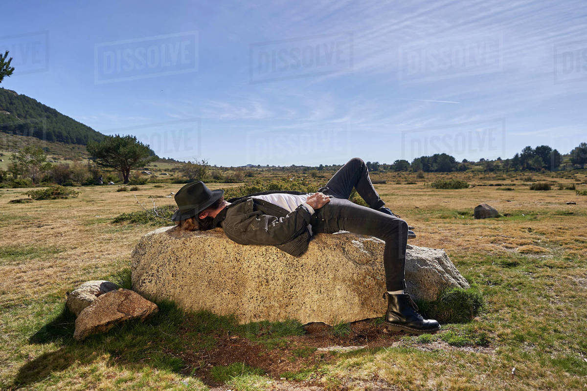 Portrait of young tattoed man lying on a rock in the countryside Royalty-free stock photo