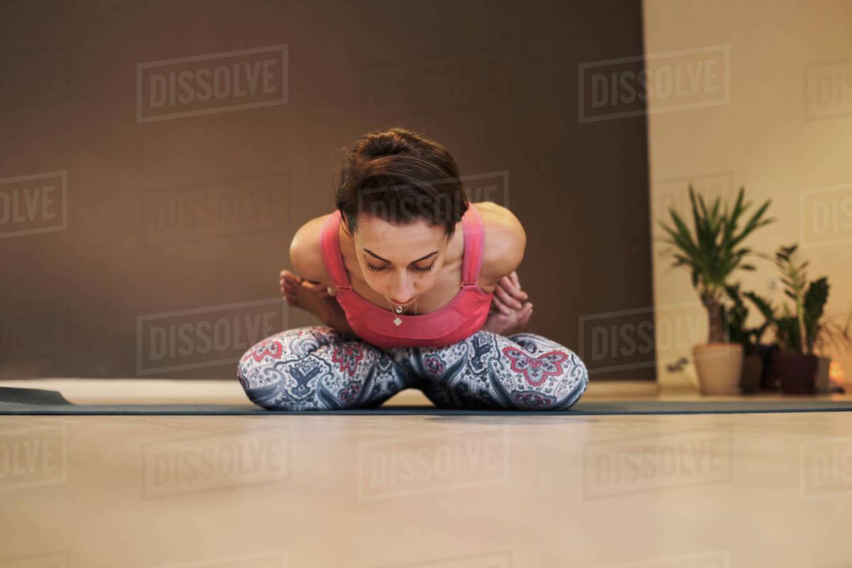 Young woman doing yoga on yoga mat in atmospheric yoga studio Royalty-free stock photo