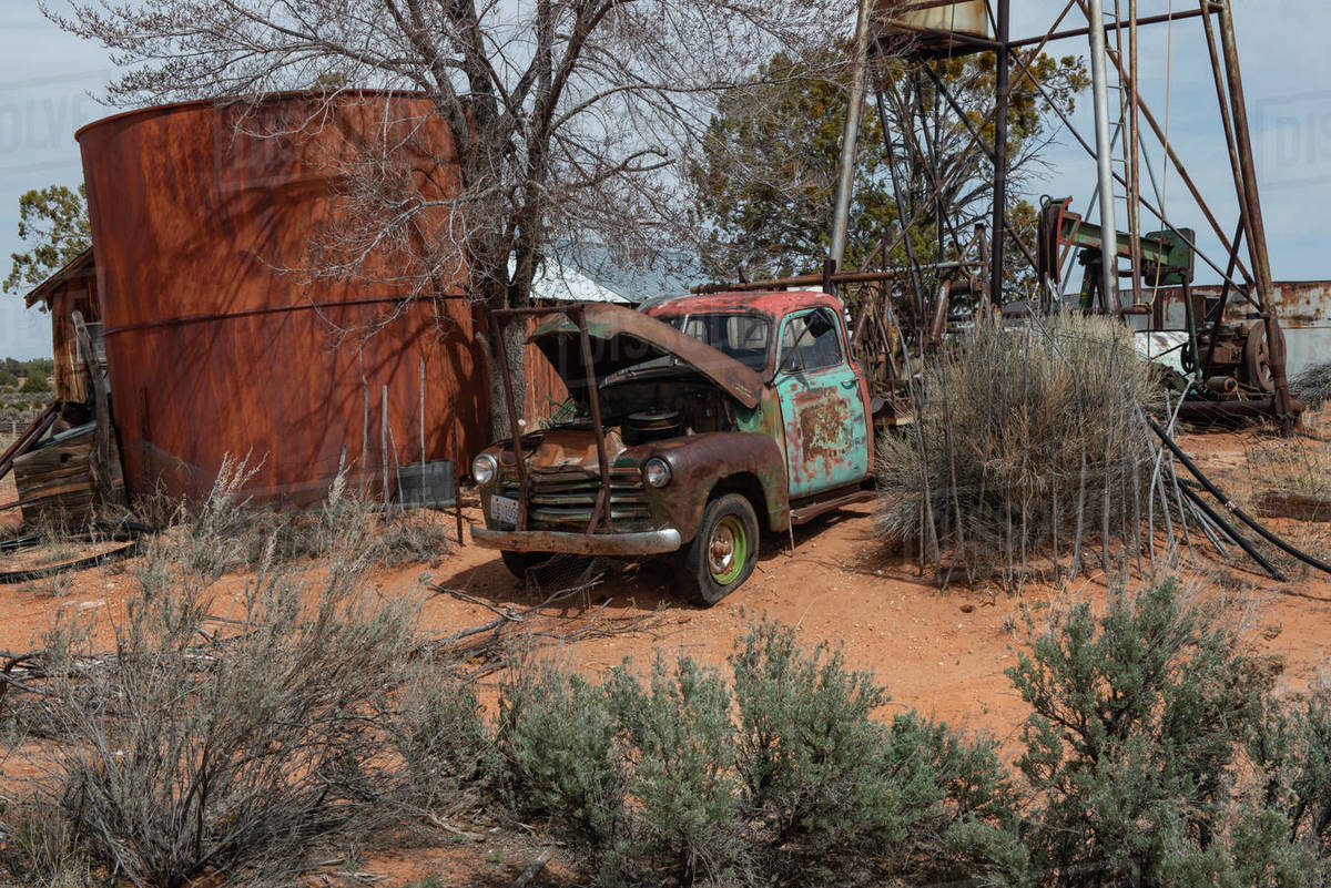 An old abandoned truck and pump jack well rusty Americana in AZ desert Royalty-free stock photo