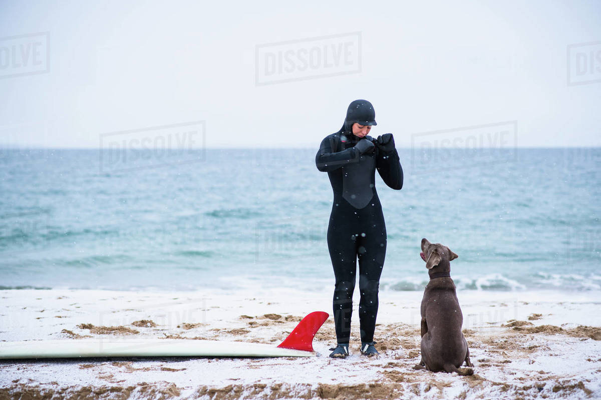 Young woman and dog going winter surfing in snow Royalty-free stock photo