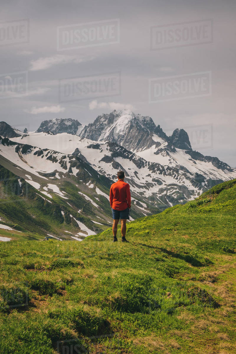 Young male stands looking at the Mont Blanc massif, Chamonix, France. Royalty-free stock photo