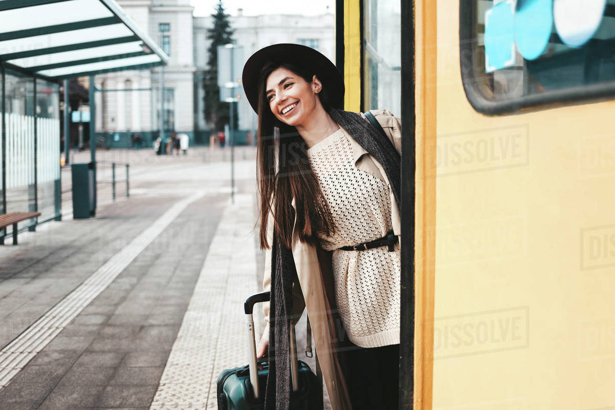 Beautiful girl tourist in coat and hat peek out of a tram door Royalty-free stock photo