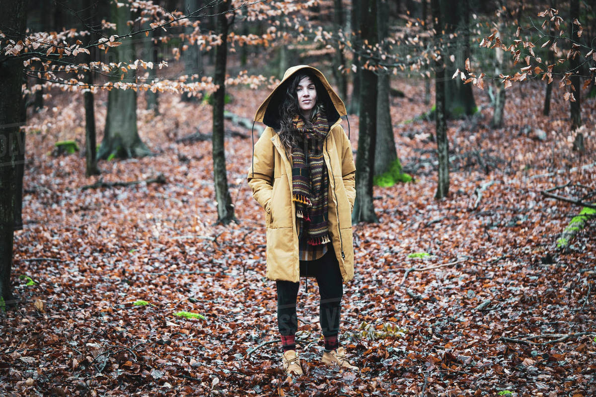 Natural young woman stands empowered and alone in autumn forrest Royalty-free stock photo