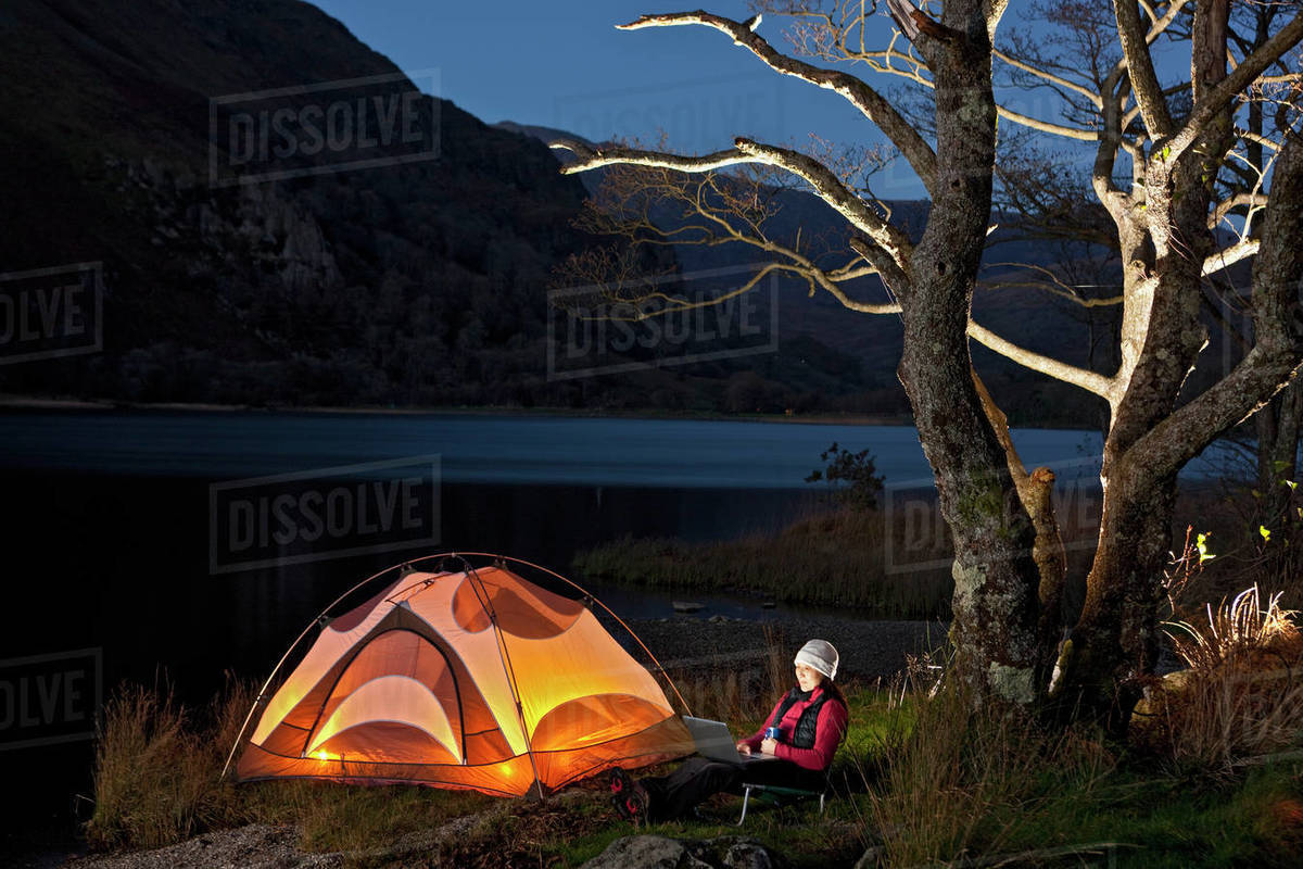 Female hiker looking at her laptop at camp in North Wales Royalty-free stock photo