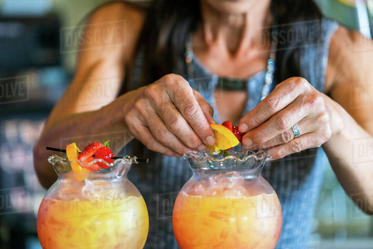 Close up of middle aged woman's hands making drinks with fruit Royalty-free stock photo