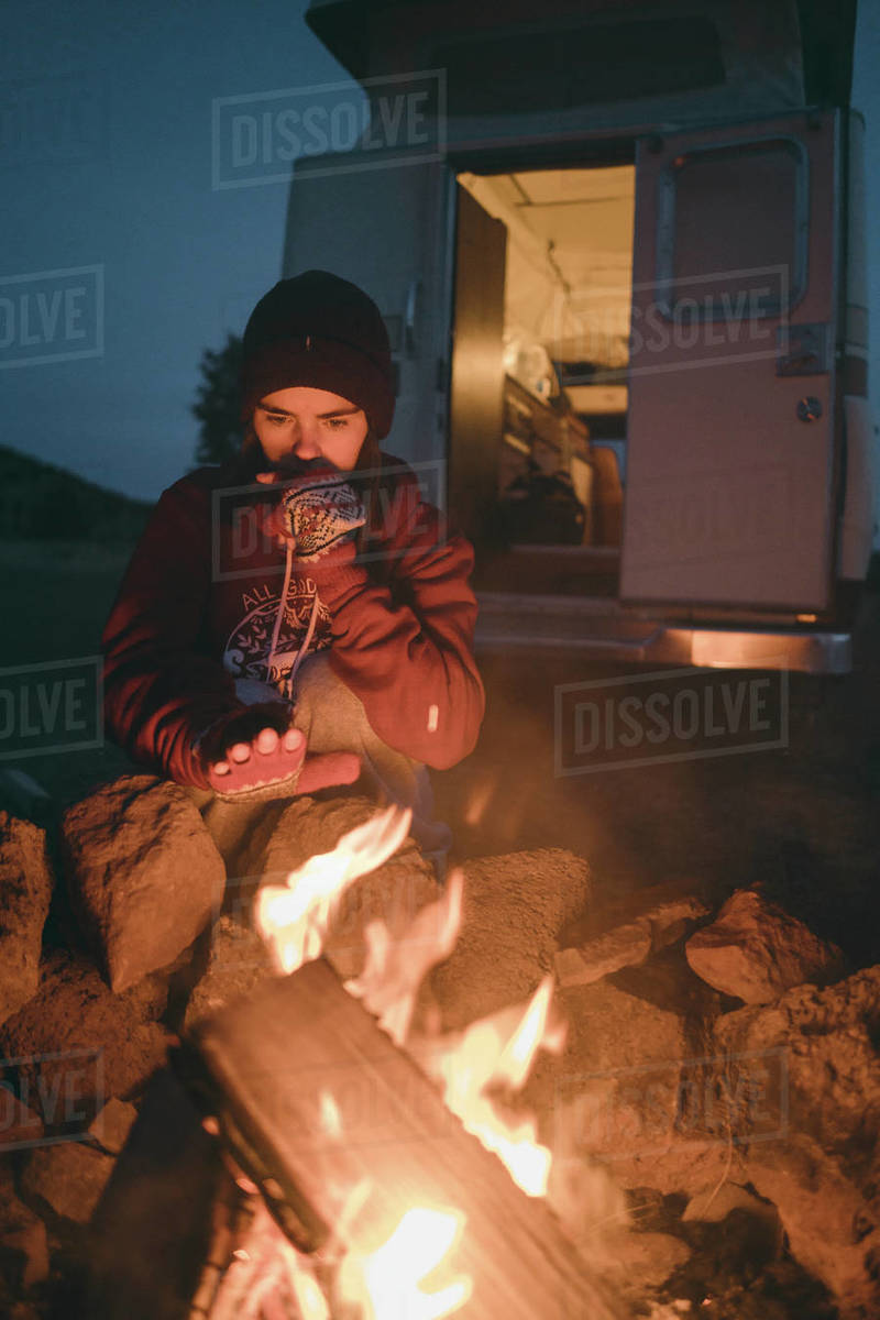 Young woman holding hands near fire while camping at dusk Royalty-free stock photo