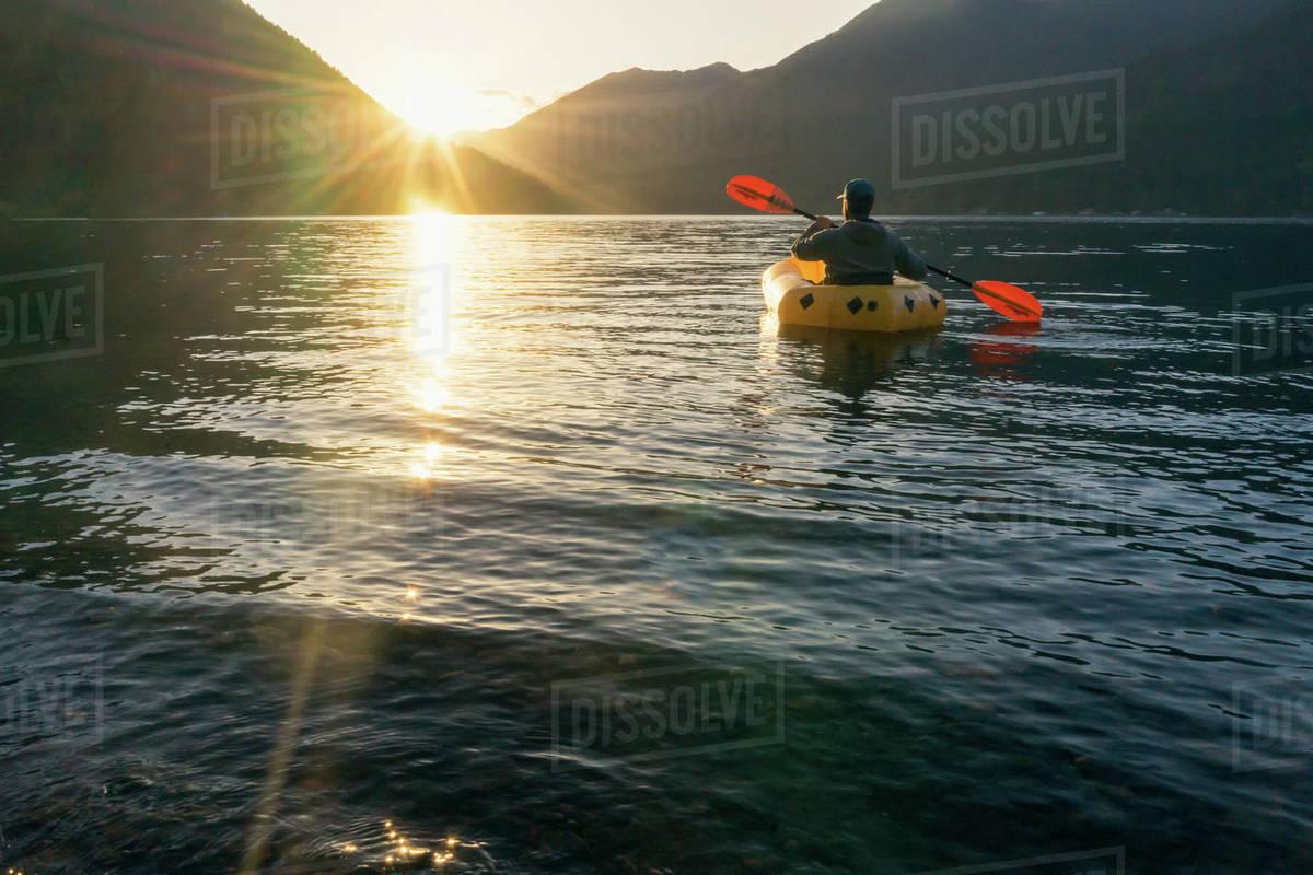 Young man paddling on lake at sunset towards mountains Royalty-free stock photo