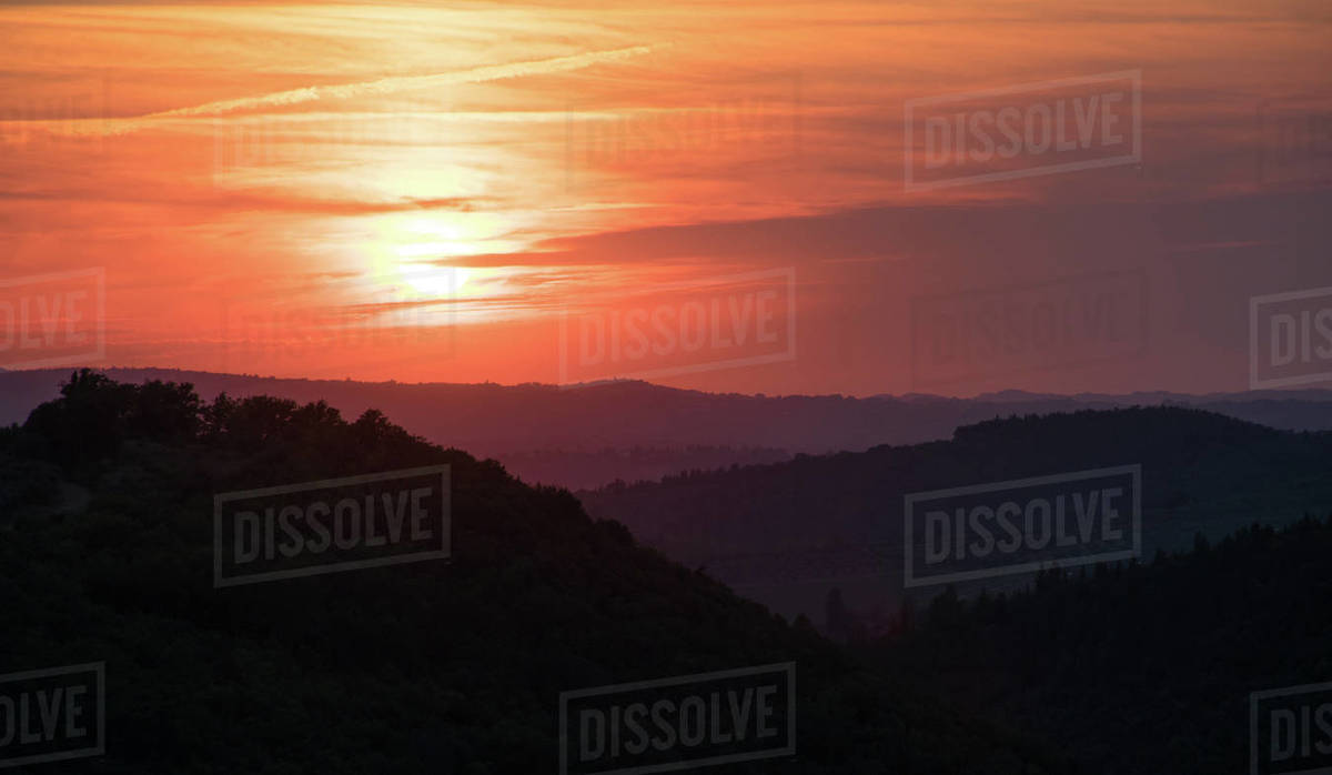 Amazing sunrise or sunset in the mountains of Tuscani, Italy. The orange sun is shining across the grey clouds and lighting the dark valleys and mountains. Horizontal photo Royalty-free stock photo
