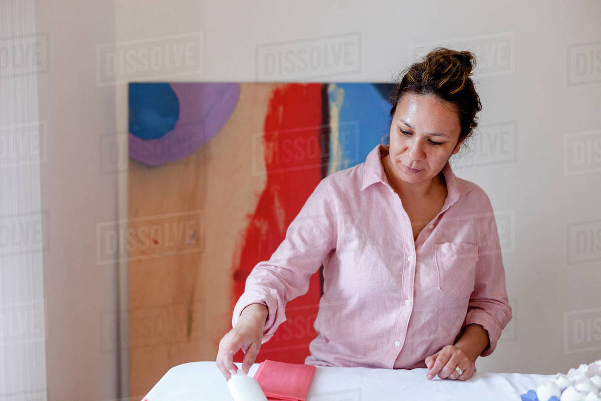 Smiling woman organizing material on table from home studio Royalty-free stock photo