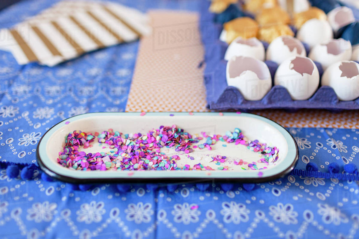 Close-up multi color confetti and eggshells over cloth table Royalty-free stock photo