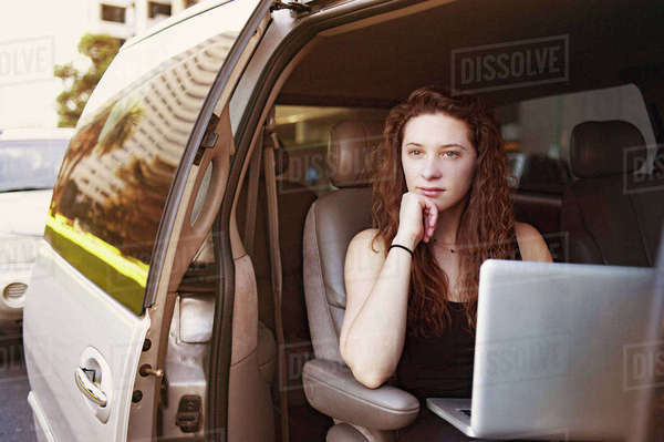 Thoughtful young woman sitting with laptop in car Royalty-free stock photo