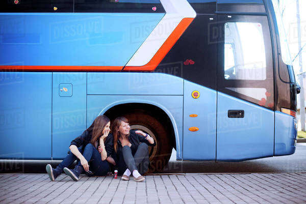 Two women sitting in front of tour bus Royalty-free stock photo