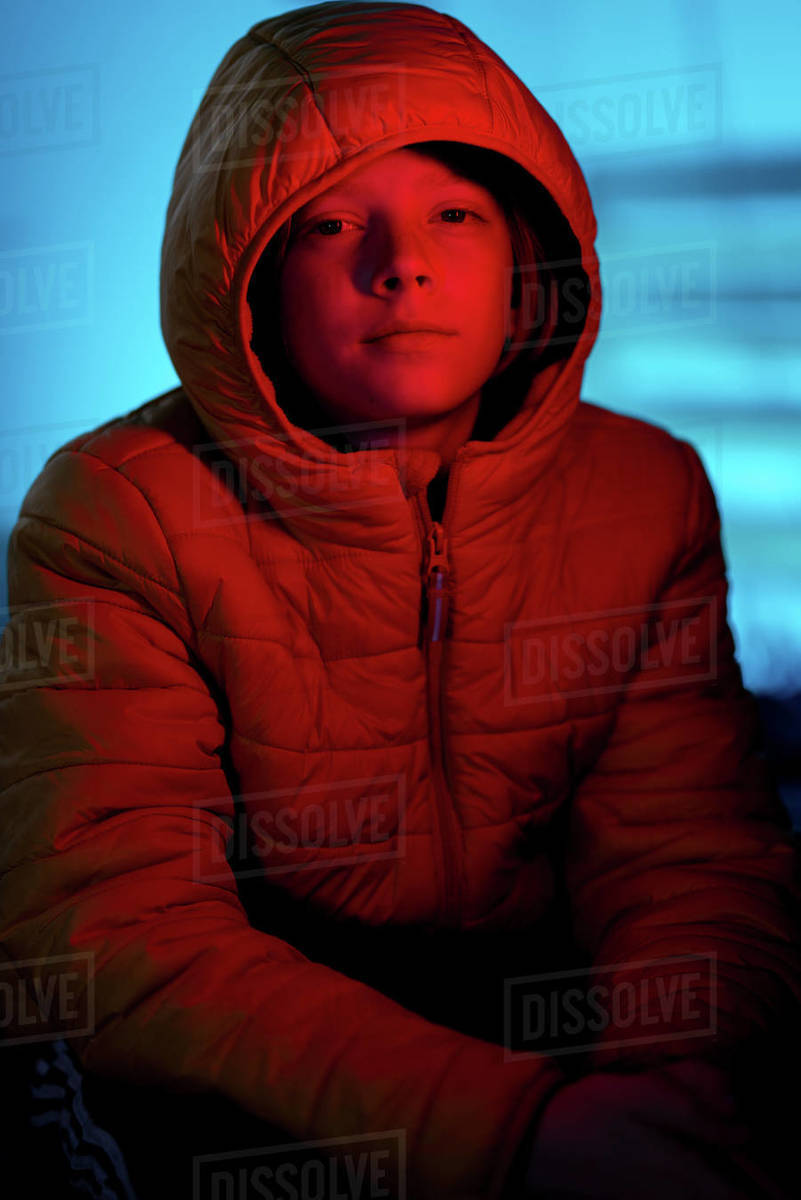 Portrait of Tween covered in red light with blue light in background Royalty-free stock photo