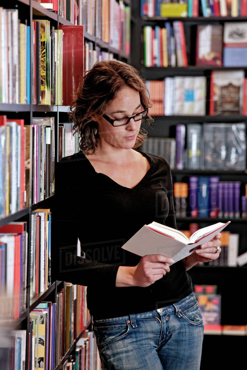 Woman reading book in bookstore Royalty-free stock photo
