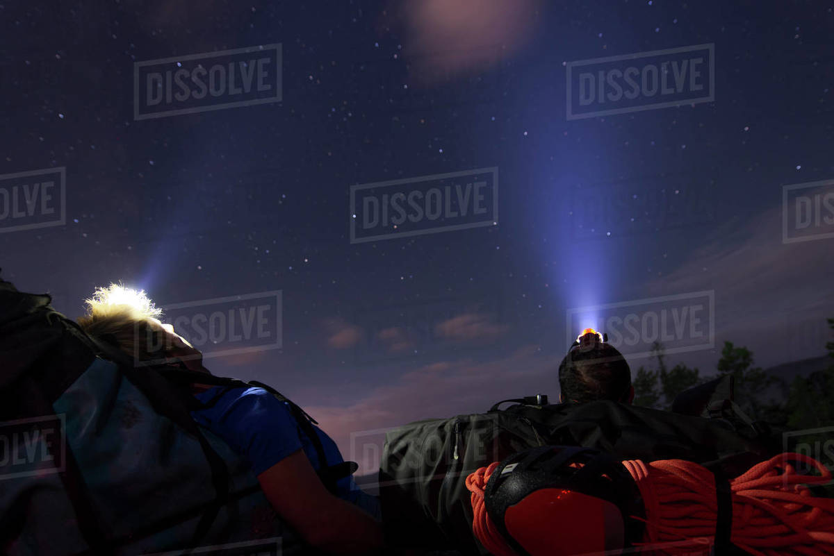 Two people laying down on backpack under the stars with headlamps Royalty-free stock photo