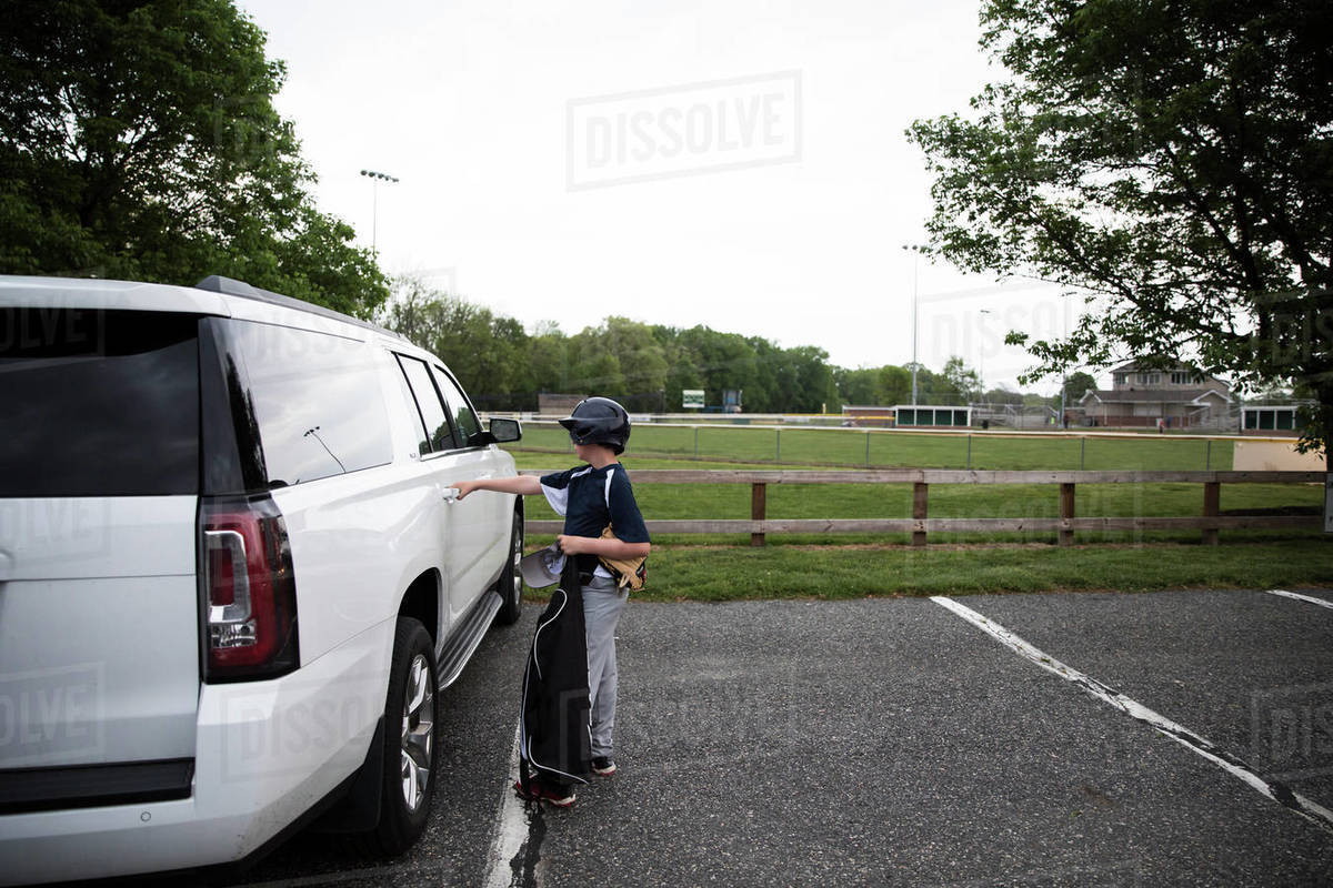 Side View of Teen Boy in Baseball Gear Opening SUV Door After Game Royalty-free stock photo