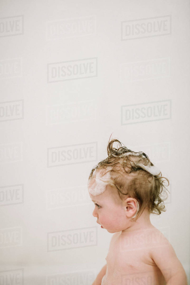 Baby in the bath with soapy hair in profile Royalty-free stock photo