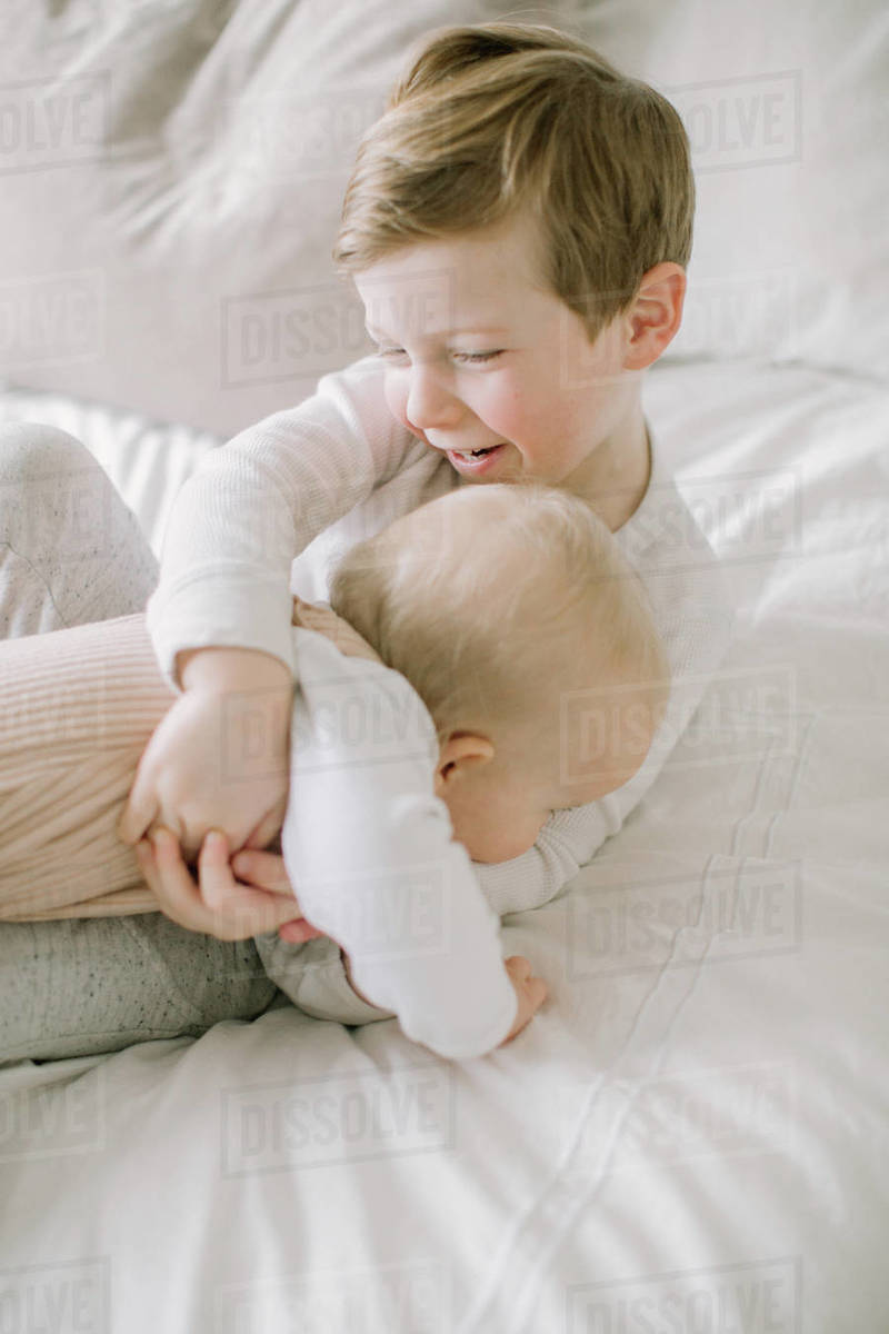 Toddler boy and baby sister playing on bed at home Royalty-free stock photo