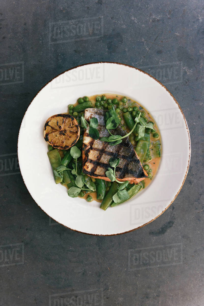 Grilled salmon filet over green harvest vegetables and lemon on table Royalty-free stock photo