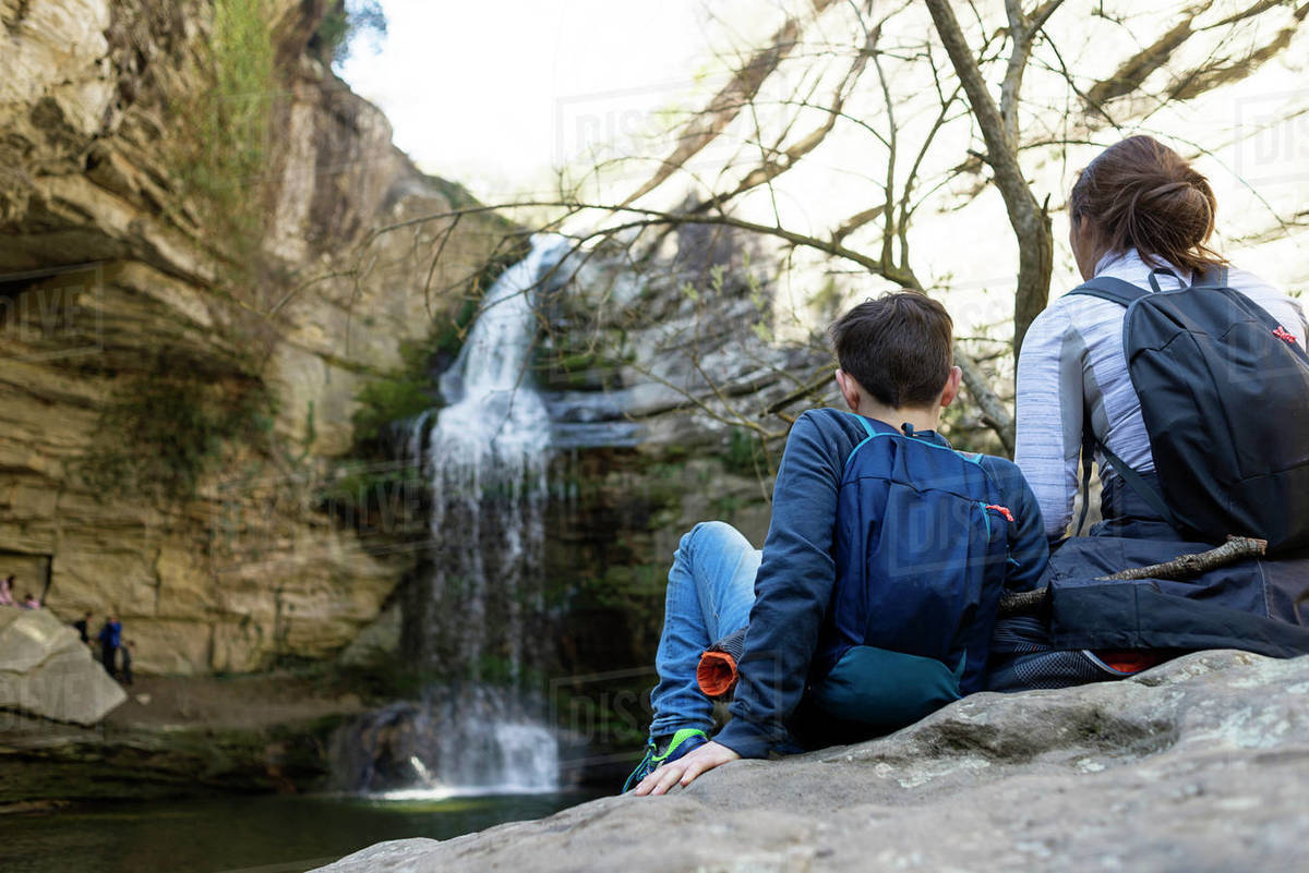 Back view of two young teenagers sitting on rock against waterfall Royalty-free stock photo