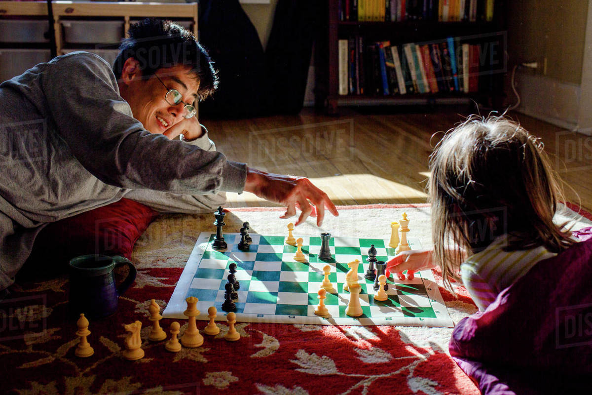 A smiling dad and his young girl play chess in a patch of bright light Royalty-free stock photo