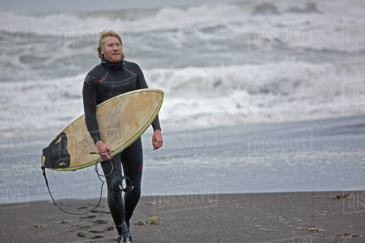 Young man walks with surfboard along beach in Iceland Royalty-free stock photo