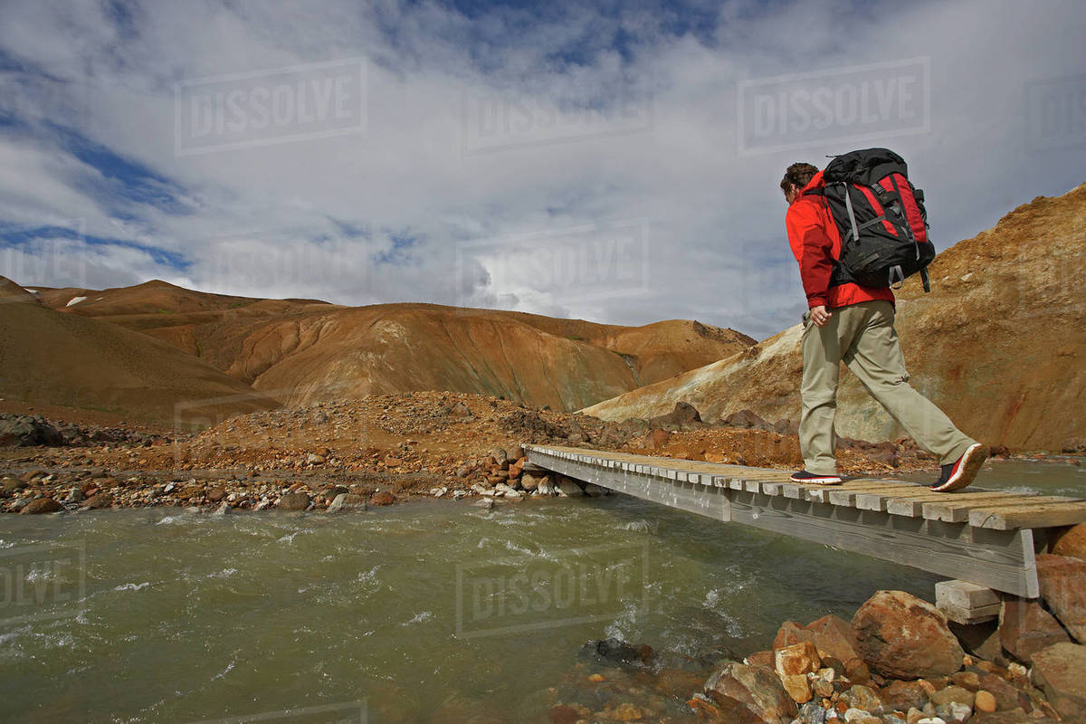 Hiker crossing wooden bridge in the Icelandic highlands Royalty-free stock photo