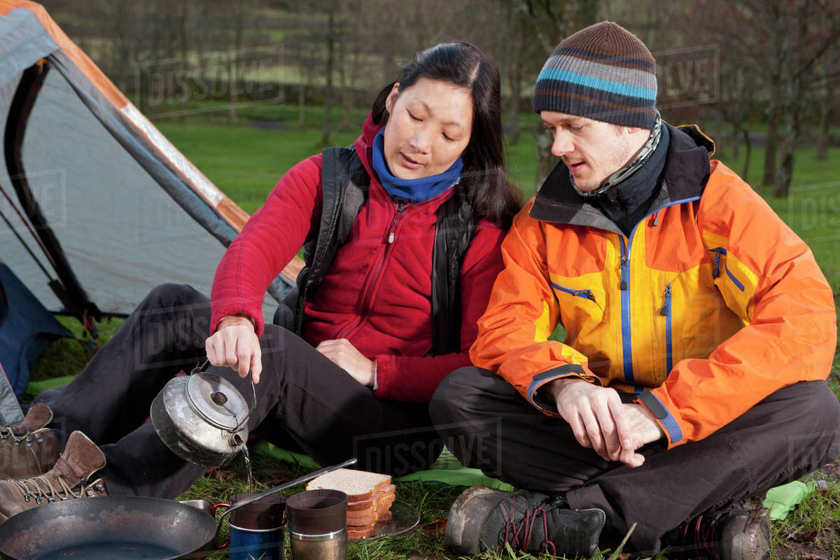 Couple preparing hot beverage at campsite in the UK Royalty-free stock photo