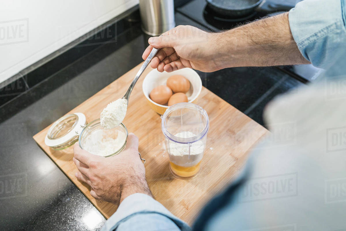 Man cooking in the kitchen in a denim shirt. An anonymous man is holding a spoon of flour Royalty-free stock photo