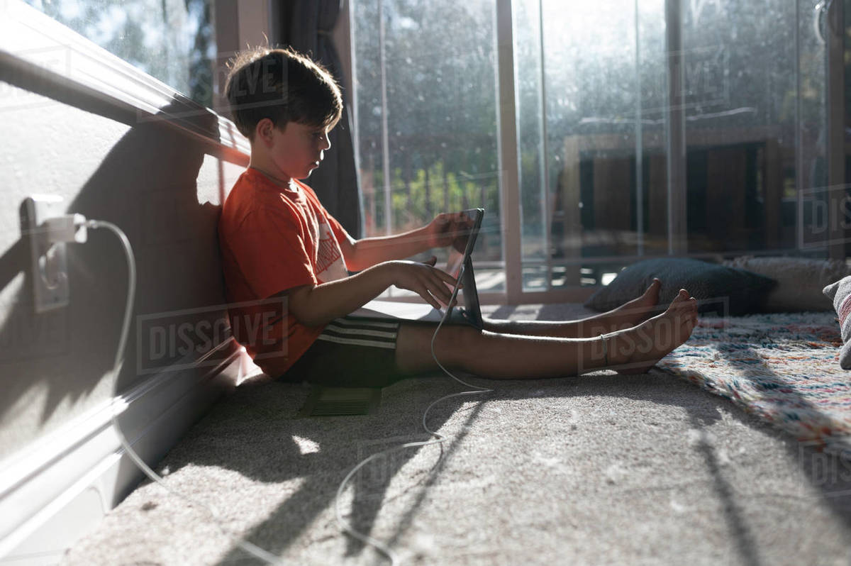 Profile of boy using ipad tablet on the floor of his home Royalty-free stock photo