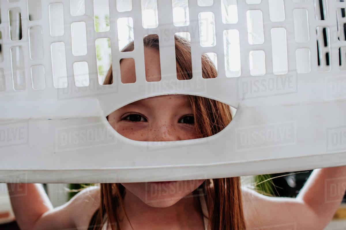 Goofy cute child peeking through laundry basket Royalty-free stock photo