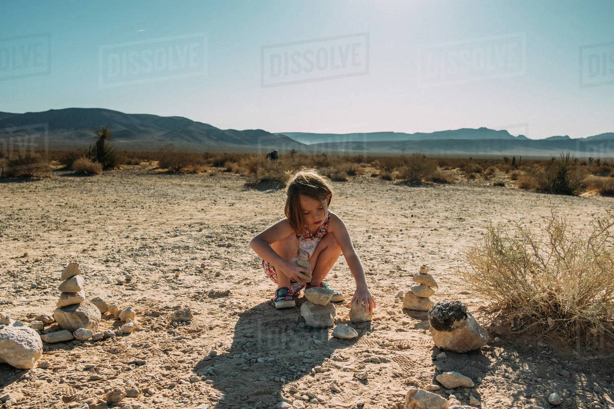Young girl building with rock in the desert Royalty-free stock photo