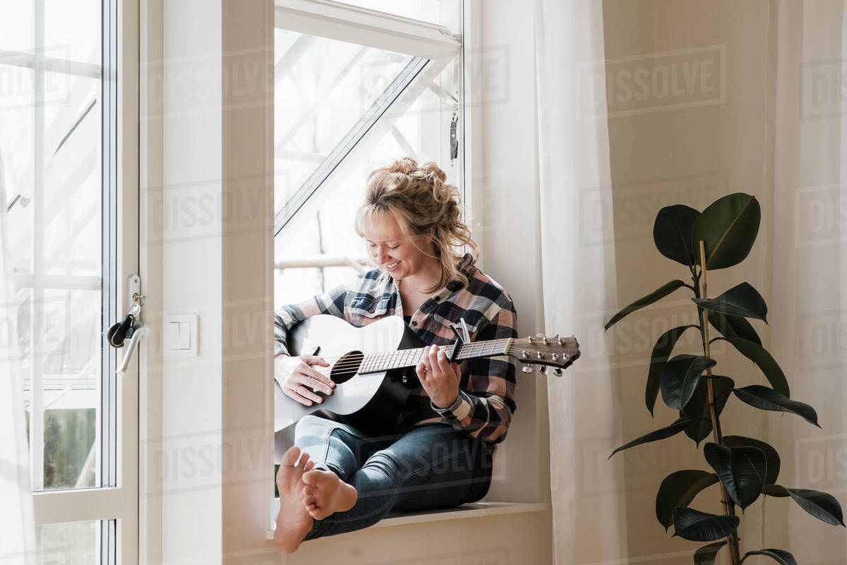 Woman sat at home on a window ledge smiling playing guitar Royalty-free stock photo