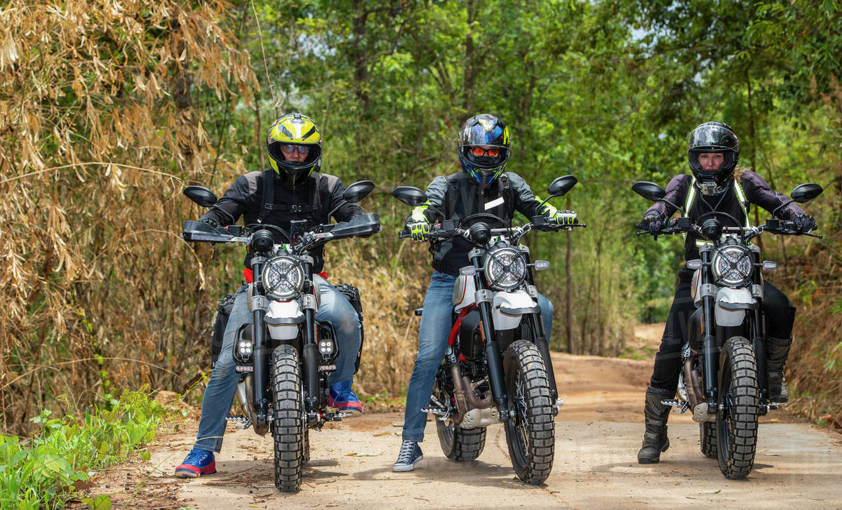 Three friends riding their scrambler motorcycles through forrest Royalty-free stock photo