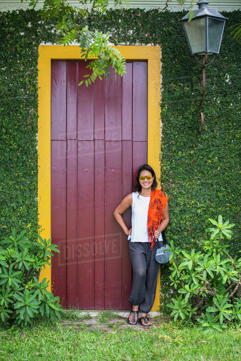 Woman posing in front of door with yellow frame in Paraty / Brazil Royalty-free stock photo