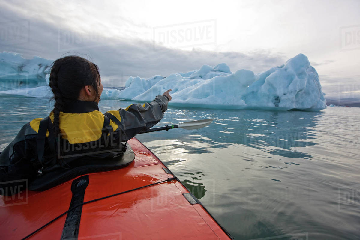 Woman rowing sea kayak on Jökulsárlón glacier lagoon in Iceland Royalty-free stock photo