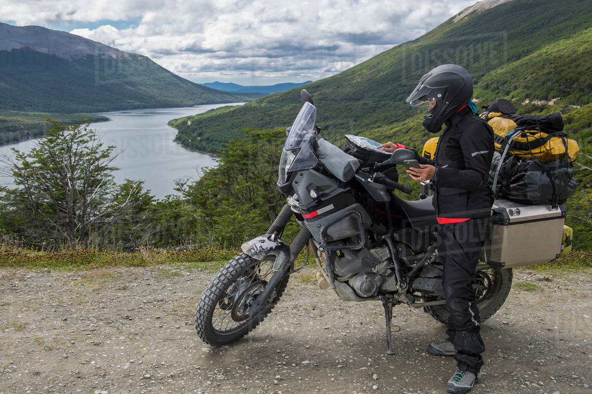 Motorbike rider is checking the map and synchronises it with her GPS Royalty-free stock photo