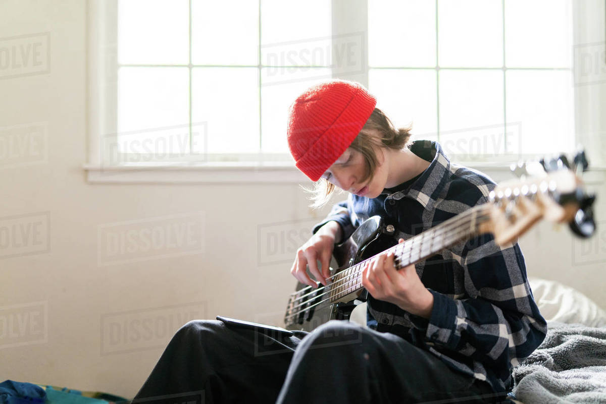 High school student working at home on learning guitar for homework Royalty-free stock photo