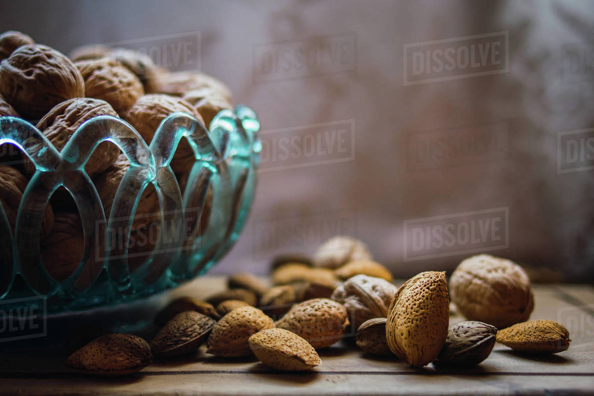 Walnuts and almonds in a blue glass bowl on a rustic wooden table Royalty-free stock photo