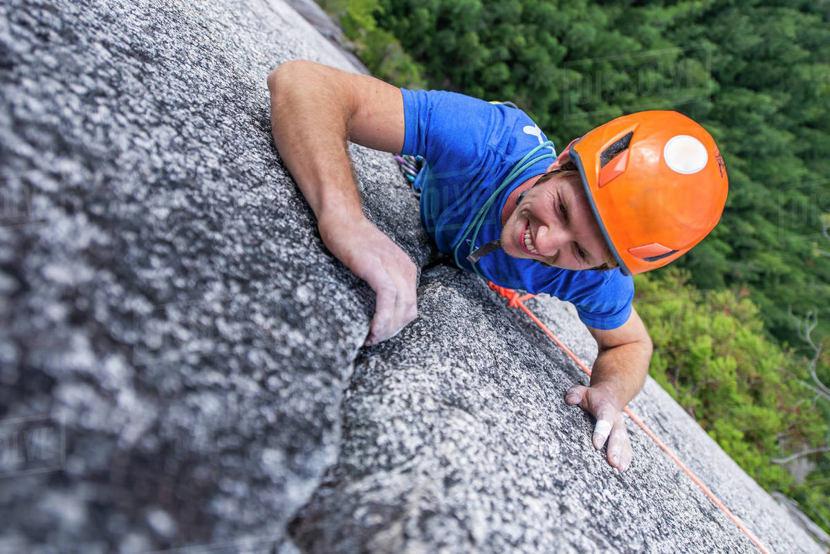 Climber looking up and laughing while rock climbing with helmet Chief Royalty-free stock photo